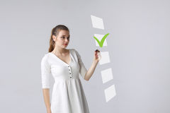 Young business woman checking on checklist box. Gray background. Stock Photo