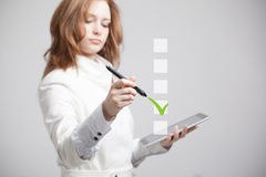 Young business woman checking on checklist box. Gray background. Stock Image