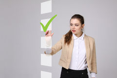 Young business woman checking on checklist box. Gray background. Royalty Free Stock Photography