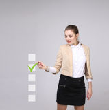 Young business woman checking on checklist box. Gray background. Royalty Free Stock Photo