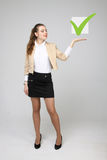 Young business woman checking on checklist box. Gray background. Stock Photos