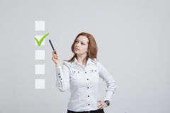 Young business woman checking on checklist box. Gray background. Royalty Free Stock Image