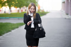 Young business woman checking time on wristwatch Royalty Free Stock Photo