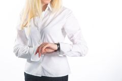 Young business woman checks time on her wrist watch, time, late concept, studio shoot isolated on white Stock Photography