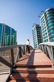 Business woman in city business center stand on bridge. Young business woman in city business center stand on bridge Royalty Free Stock Image