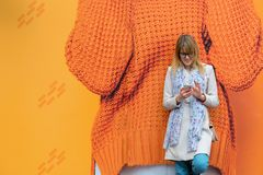 A young business woman in the city on the street reads messages. On the phone Stock Photography