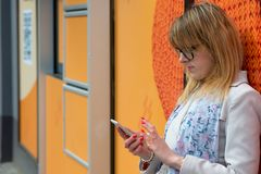 A young business woman in the city on the street reads messages. On the phone Royalty Free Stock Photo