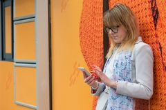 A young business woman in the city on the street reads messages. On the phone Stock Photos