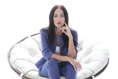 Portrait of a young woman in a blue suit sitting on a soft chair Royalty Free Stock Images