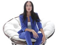 Portrait of a young woman in a blue suit sitting on a soft chair Stock Photo