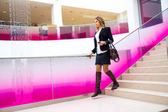 Young business woman coming down the stairs. In the office Royalty Free Stock Photos
