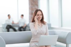 Young business woman communicates with her partners using laptop and smartphone. People and technology stock images