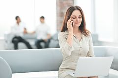 Young business woman communicates with her partners using laptop and smartphone. People and technology royalty free stock photography