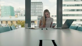 Young business woman in conference room with papers. Elegant blond woman sitting at long table in modern hall of office. Elegant blond woman sitting at long stock footage