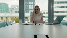 Young business woman in conference room with papers. Elegant blond woman sitting at long table in modern hall of office. Elegant blond woman sitting at long stock video footage