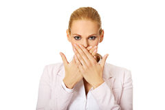 Young business woman covering her mouth with two hands Royalty Free Stock Image