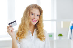 Young business woman with a credit card. On a light background Stock Image