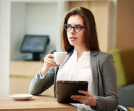 Young business woman with a cup of coffee working in office Royalty Free Stock Image