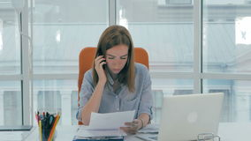 Young business woman at desk with phone and computer in modern office. stock video