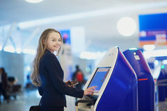 Young business woman doing self check-in in international airport terminal Royalty Free Stock Photography