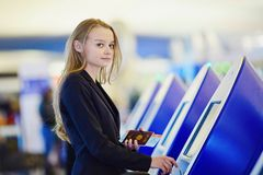 Young business woman doing self check-in in international airport terminal Royalty Free Stock Photo
