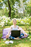 Young business woman doing yoga outside office building sitting in lotus position in the park with her laptop and cup of tea or co Royalty Free Stock Images