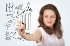 Young business woman drawing diagrams on whiteboard Stock Photos