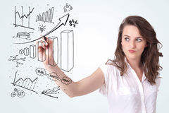 Young business woman drawing diagrams on whiteboard Royalty Free Stock Images