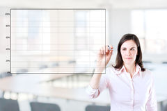 Young business woman drawing on empty graph. Young business woman drawing on empty graph 2. Office background Royalty Free Stock Photography