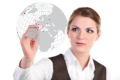 Young business woman drawing on glass. Young business woman drawing with a red pencil on a world map Stock Image