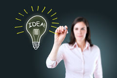 Young business woman drawing a light bulb. Stock Photos