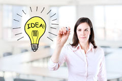 Young business woman drawing a light bulb. Stock Photo