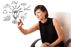 Young business woman drawing light bulb with various diagrams an. D charts on whiteboard isolated on white Royalty Free Stock Photos