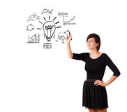 Young business woman drawing light bulb with various diagrams an. D charts on whiteboard isolated on white Royalty Free Stock Photo