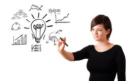 Young business woman drawing light bulb with various diagrams an. D charts on whiteboard isolated on white Royalty Free Stock Images