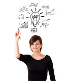 Young business woman drawing light bulb with various diagrams an. D charts on whiteboard isolated on white Stock Photography