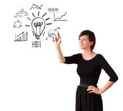 Young business woman drawing light bulb with various diagrams an Stock Images
