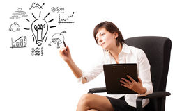 Young business woman drawing light bulb with various diagrams an Stock Photo