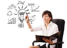 Young business woman drawing light bulb with various diagrams an. D charts on whiteboard isolated on white Stock Photo
