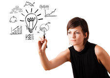 Young business woman drawing light bulb with various diagrams an Royalty Free Stock Image