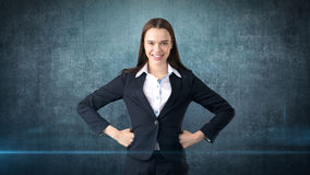Young business woman dress in black suit and white shirt is standing, holding her hands on hips with copyspace. Royalty Free Stock Photo