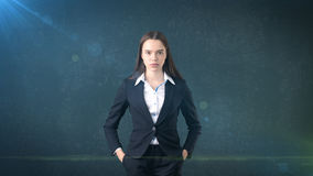 Young business woman dress in black suit and white shirt is standing, holding her hands on hips. Royalty Free Stock Photography