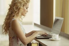 Young business woman in dress sitting at table in cafe, looking on screen of laptop. On table notebook and cup of coffee. Freelancer working. Student learning stock photography
