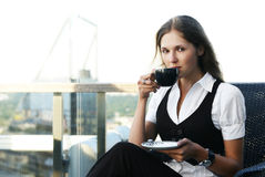 A young business woman is drinking coffee Stock Photos