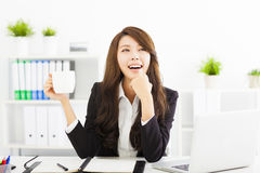 Young business woman drinking coffee in office Stock Photos