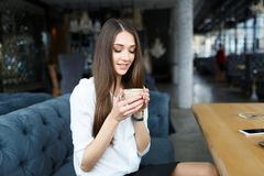 Young business woman drinking coffee in the restaurant . Laptop and smartphone on the table. Business concept Royalty Free Stock Images