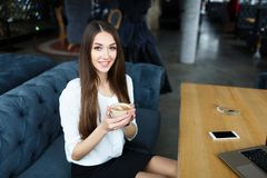 Young business woman drinking coffee in the restaurant . Laptop and smartphone on the table stock photos