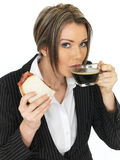 Young Business Woman Eating a Bacon Sandwich and Black Coffee Stock Photography