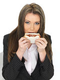 Young Business Woman Eating a Bacon Sandwich Royalty Free Stock Image