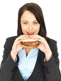 Young Business Woman Eating a Beef Burger Royalty Free Stock Photography